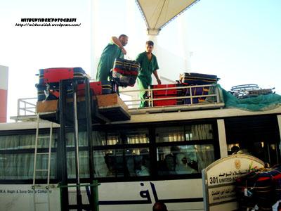 Para pekerja haji sedang memunggah beg-beg dan kelengkapan ke atas bumbung bas sebelum bertolak ke Mina.