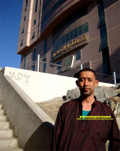 Datuk Misbun bergambar kenangan membelakangkan bangunan Tabung Haji di Mekah.