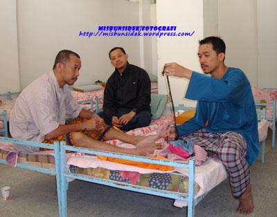 Rashid sedang memperkatakan sesuatu kepada Jalani dan Rahman dengan tasbih yang baru dibelinya.